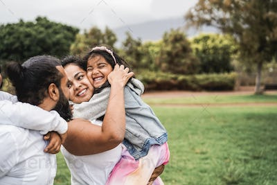 Happy indian family having fun outdoor at city park - Main focus on girl face
