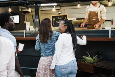 Multiracial people ordering gourmet food in front of food truck outdoor