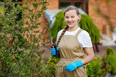 A beautiful young woman in gardening gloves is pruning the branches of plants