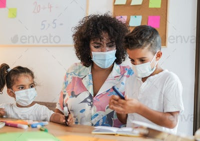Teacher and children in class room while wearing surgical face mask for coronavirus