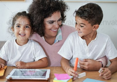 Mother and children using tablet at home indoor - Homeworks or home schooling