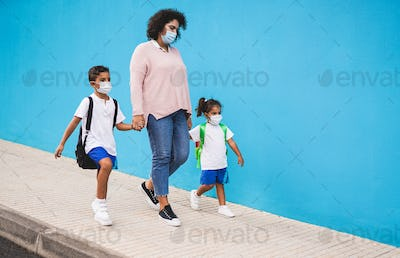 Mother walking and holding hands of children while wearing surgical face mask