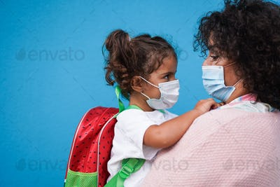 Mother hugging her daughter going back to school while wearing surgical face masks