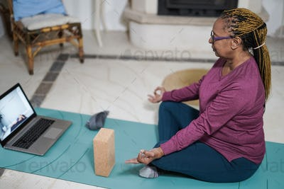 African senior woman doing meditation with laptop at home indoors
