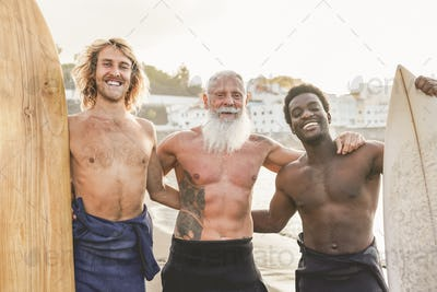 Multiracial surfer men on the beach with surfboard