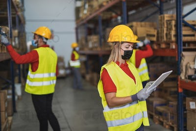 Young woman at work in warehouse with digital tablet scanner while wearing protective face mask