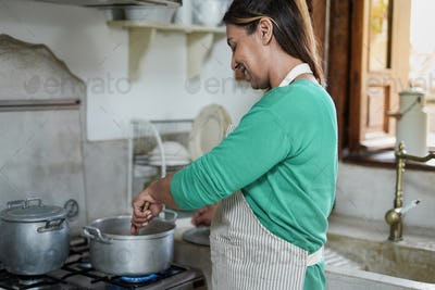 Happy mature latin woman cooking soup at home in vintage kitchen