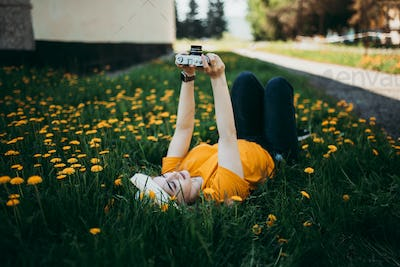 Young beautiful girl in an orange T-shirt holding retro camera in her hands lying on the lawn where