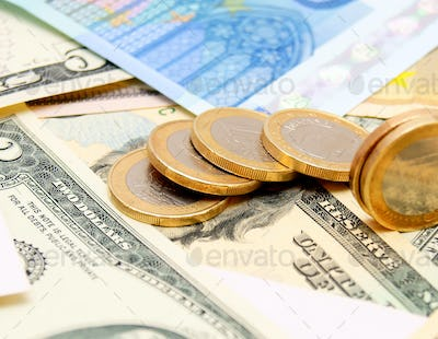 Coins on money (dollars and euro).