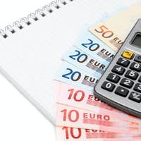 Money (euro) and the calculator for a notebook.