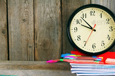 Watches and school tools. On wooden background.