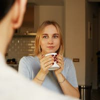 Conversation of confident man and young blond woman at home
