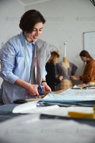 Dress designer cutting a fabric sheet with scissors