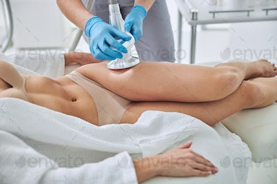 Unrecognized female in white bathrobe receiving anti-cellulite and anti-fat therapy in beauty clinic