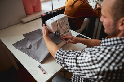 Male tailor sewing grey cloth with a machine