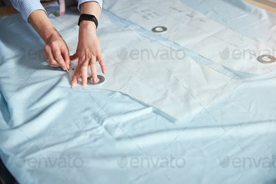 Person drawing with chalk around sewing pattern