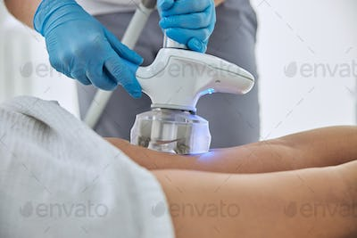 Unrecognized female client receiving anti-cellulite and anti-fat therapy in beauty clinic