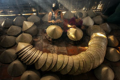 Top view of Two Vietnamese sisters craftsman making the traditional vietnam hat