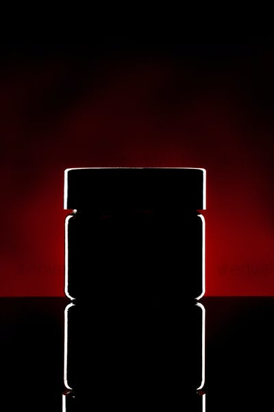 Plastic jar with cosmetics illuminated on dark background