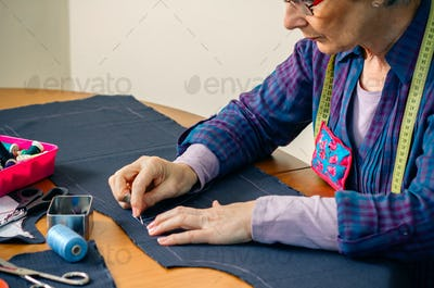 Senior female seamstress sewing cloth