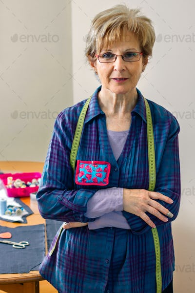 Senior dressmaker posing with sewing materials