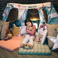 Girl hugging stuffed doll playing in a diy tent at home