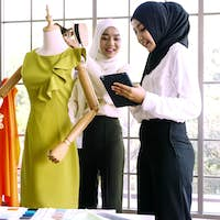 Beautiful muslim women working together at the clothing office.