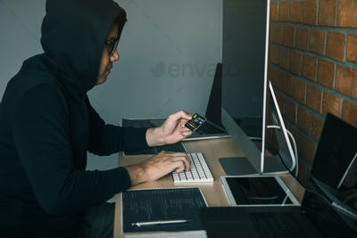 Hacker in the hood working with computer and holding credit card with payment hacking concept.