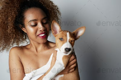 Young black african female with afro hair hugging her puppy basenji dog. Love between dog and owner.