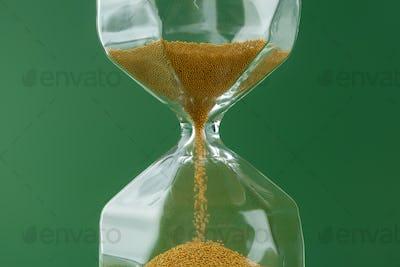 Gold hourglass on dark green paper background
