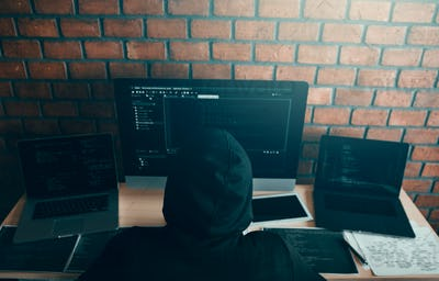 Hacker in the hood working with computer with hacking breaking into data servers.