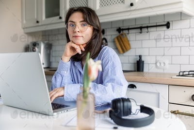Young beautiful woman works from a home with a laptop on a white desk as a freelancer