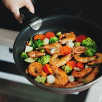 Woman cooking vegetables and shrimps on pan