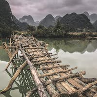 Old dangerous abandonned bamboo bridge crossing a river in the