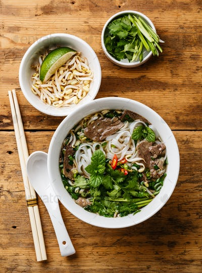 Pho Bo vietnamese Soup with beef and  soybean seedlings on wooden background
