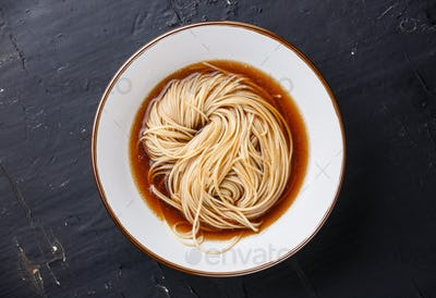 Asian Ramen noodles with broth in bowl on dark background