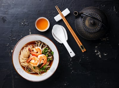 Asian Ramen noodles with broth in bowl serving size and Tea on dark background
