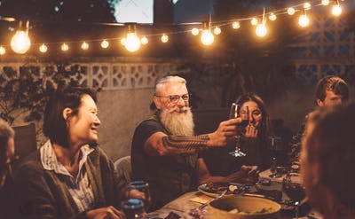 Happy family dining and tasting red wine glasses in barbecue dinner party