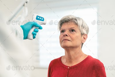 Doctor measuring temperature with new digital thermometer to senior woman patient