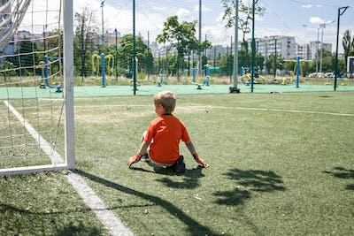 Little boy in black and orange soccer form playing football on open field in yard, young goalkeeper