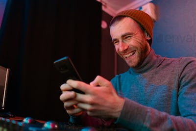 Laughing Man portrait holding smartphone in his office in neon lights