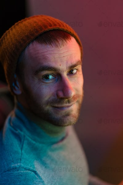 Portrait of an Caucasian hipster man, blue and red lights
