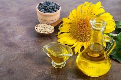 Golden oil in a glass jug, sunflower, sunflower seeds