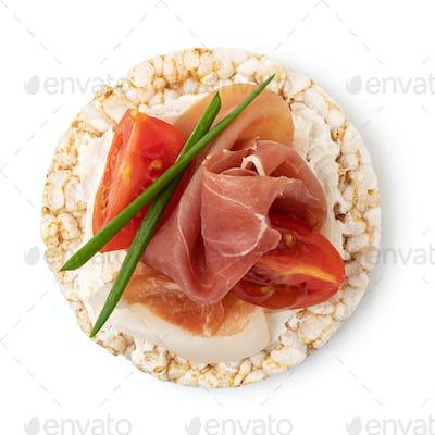 Rice cakes with cream cheese, prosciutto and tomato