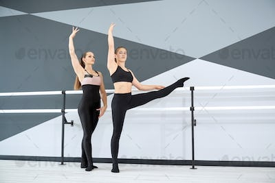 Instructor helping girl in learning choreographic move