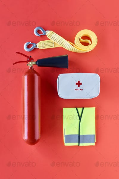 top view of fire extinguisher, car tow rope, reflective vest and first aid kit on red backdrop