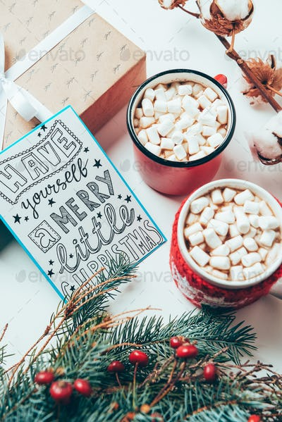 top view of postcard with have yourself marry little christmas lettering, present and cups of cocoa
