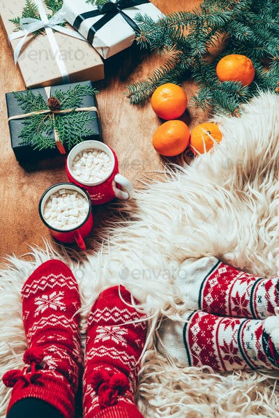 cropped shot of women in winter socks at background with wrapped christmas presents and cups of hot