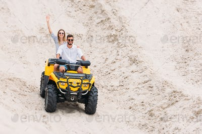 happy young couple riding ATV in desert and waving at camera