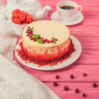close up of cake decorated with currants and mint leaves near tea pot and cup of strawberries on